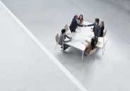 Businessmen in meeting shaking hands across table - CAIF01141