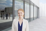 Portrait of smiling businesswoman outside building - CAIF01144