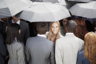 Portrait of smiling businesswoman surrounded by crowd with umbrellas - CAIF01174