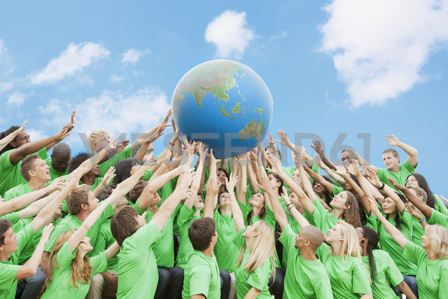 Team in green t-shirts lifting globe overhead - CAIF01180