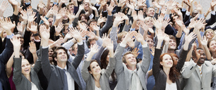 Crowd of business people cheering with arms raised - CAIF01189