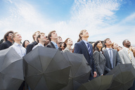 Crowd of business people with umbrellas looking up at sky - CAIF01192