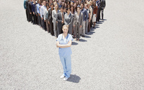 Portrait of confident nurse with business people in background - CAIF01195