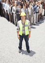 Portrait of smiling construction worker with business people in background - CAIF01198