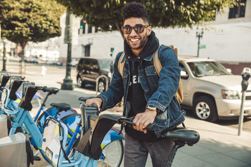 Stylish young man on the street with rental bike - SUF00473