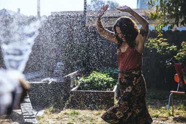 Water splashing on young woman in backyard - SUF00485