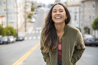 Portrait of laughing young woman on the street - SUF00506