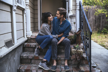 Happy couple sitting on stoop embracing - SUF00512