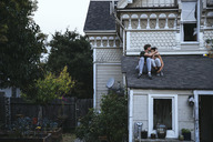 Couple sitting on roof kissing - SUF00518