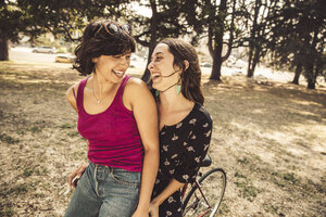 Two happy young women on bicycle - SUF00524
