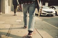 Low section of man walking on sidewalk with skateboard - SUF00527