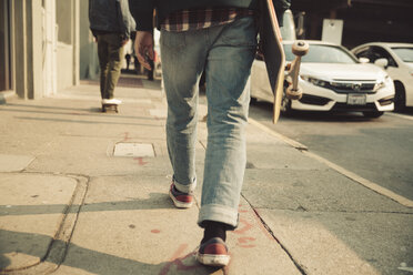 Low section of man walking on sidewalk with skateboard - SUF00527