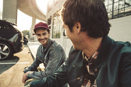 Two smiling young men sitting on sidewalk - SUF00530