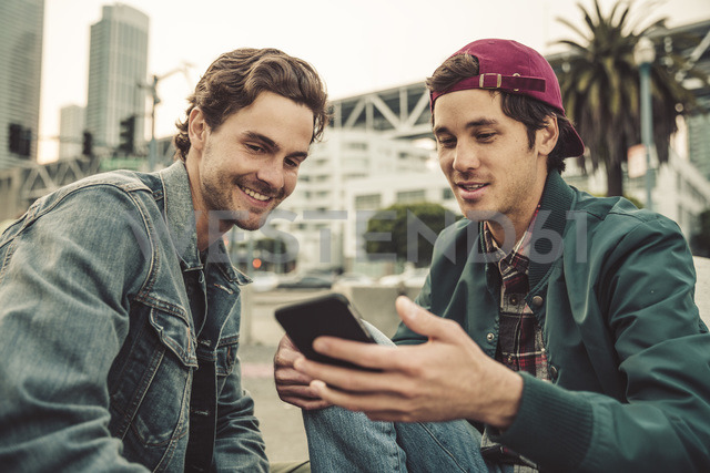Two smiling young men sharing cell phone outdoors - SUF00536 - Sullivan/Westend61