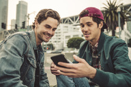 Two smiling young men sharing cell phone outdoors - SUF00536