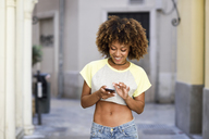 Smiling woman with afro hairstyle using smartphone outdoors - JSMF00005