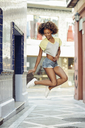Happy woman with afro hairstyle jumping in a lane - JSMF00008