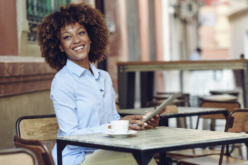 Smiling woman with afro hairstyle sitting in outdoor cafe with tablet - JSMF00014