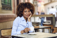 Portrait of smiling woman with afro hairstyle sitting in outdoor cafe - JSMF00017