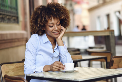 Smiling woman with afro hairstyle sitting in outdoor cafe - JSMF00020