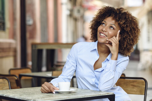 Smiling woman with afro hairstyle sitting in outdoor cafe - JSMF00023