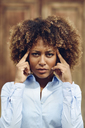 Portrait of serious woman with afro hairstyle thinking outdoors - JSMF00029