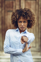Portrait of serious woman with afro hairstyle pointing with her finger outdoors - JSMF00032