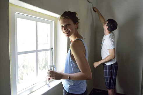 Young couple renovating their home painting the wall together - ECPF00183
