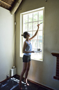 Young woman renovating her home painting the window frame - ECPF00186