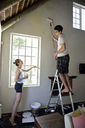 Young couple renovating their home painting the wall together - ECPF00192