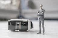 Miniature businessman figurine standing next to VR glasses - FLAF00140