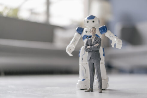 Miniature businessman figurine standing in front of robot - FLAF00143