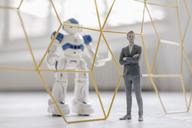 Miniature businessman figurine standing in front of robot with laptop seperated by structure - FLAF00146