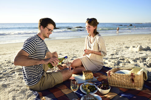 Happy couple having a picnic on the beach - ECPF00207