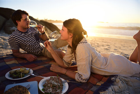 Happy couple having a picnic on the beach at sunset - ECPF00216