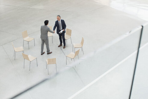 Circle of chairs around businessmen shaking hands - CAIF01227