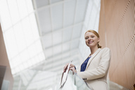Portrait of smiling businesswoman holding report in modern office - CAIF01233