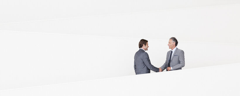 Businessmen shaking hands on modern staircase - CAIF01236