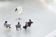 Businesswoman at flipchart leading meeting in lobby - CAIF01266