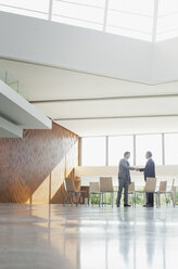 Businessmen shaking hands at circle of chairs in lobby - CAIF01272