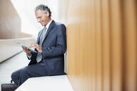 Businessman using digital tablet in office - CAIF01299