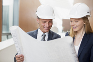 Architects wearing hard-hats and reviewing blueprints - CAIF01308
