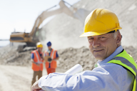 Businessman wearing hard hat in quarry - CAIF01335