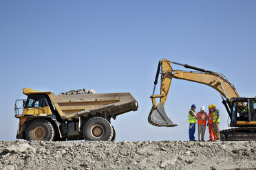 Workers talking by machinery in quarry - CAIF01419