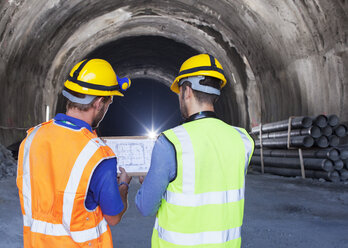 Workers reading blueprints in tunnel - CAIF01428