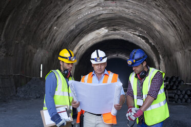 Workers and businessman with blueprints in tunnel - CAIF01434