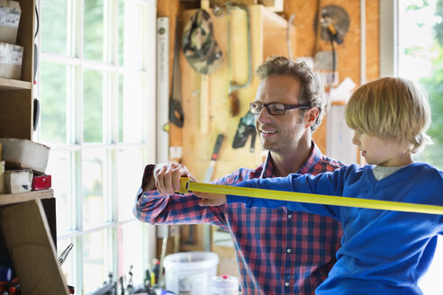 Father and son working in garage - CAIF01437