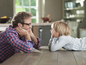Father and son admiring each other at table - CAIF01440