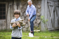 Boy carrying pile of firewood outdoors - CAIF01443