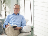 Man reading book on porch swing - CAIF01446